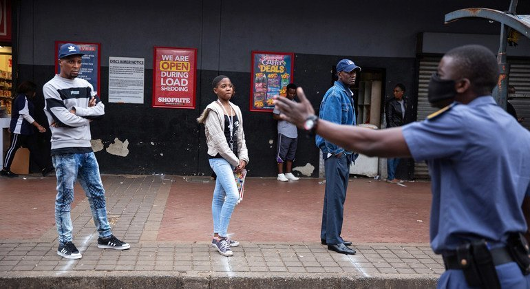 Police order shoppers queueing up outside a shop to maintain a safe distance from each other in Hillbrow, Johannesburg, South Africa, 30 March 2020