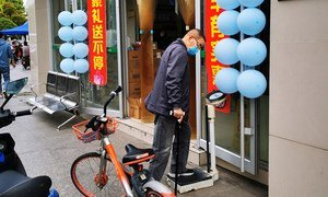 A resident weighing himself on a scale outside a drug store. in Wuhan, China, on April 8, when the lockdown of the city was ended after 76 days. Scales outside drug stores are pretty common in China.