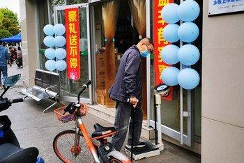 चीन के वूहान में एक मेडिकल स्टोर के बाहर 8 अप्रैल को एक व्यक्ति अपना वज़न तौलता हुआ. उस दिन वहाँ 76 दिनों के बाद तालाबन्दी ख़त्म हुई थी. चीन में मेडिकल स्टोर्स के बाहर वज़न तौलने वाली मशीन होना एक आम बात है.