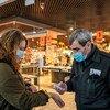 Un trabajador de un centro comercial chequea la temperatura de una cliente en Kiev, Ucrania.