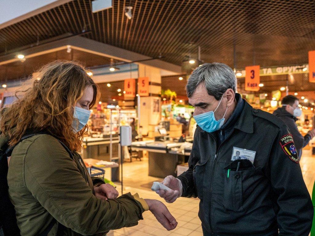Les clients sont contrôlés contre la fièvre à l'entrée des magasins. Le port du masque à l'intérieur d'un magasin est obligatoire à Kiev, en Ukraine