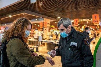 يتم فحص الزبائن أمام المحال التجارية وإلزامهم بارتداء قناع الوجه في العاصمة الأوكرانية كييف.