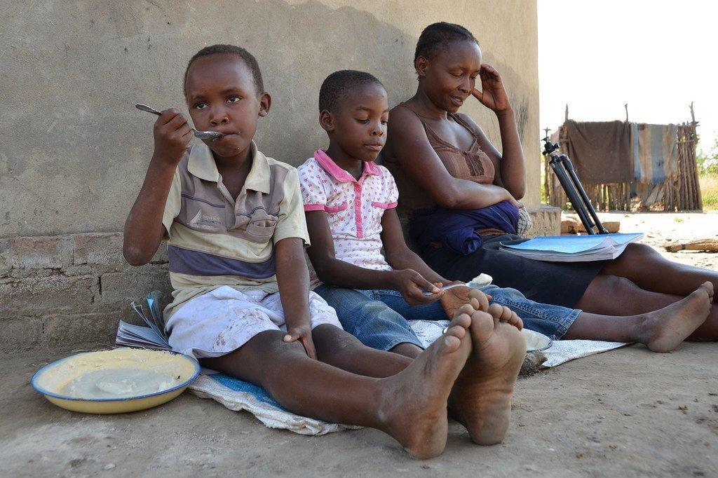 Mama akiwafundisha wanae katika wilaya ya Shamva nchini Zimbabwe wakati wa mlipuko wa COVID-19.