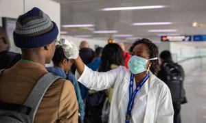 काँगो गणराज्य में माया माया अंतरराष्ट्रीय हवाई अड्डे पर यात्रियों की जाँच करते हुए स्वास्थ्यकर्मी - स्वयंसेवक
