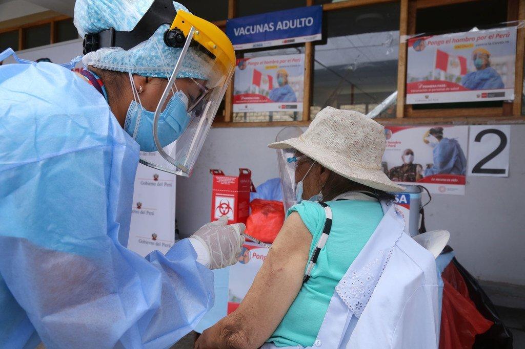 Mhudumu wa afya akimpatia chanjo mtu mmzima katika mji wa Lima nchini Peru mwishoni mwa mwezi Mechi 2021.