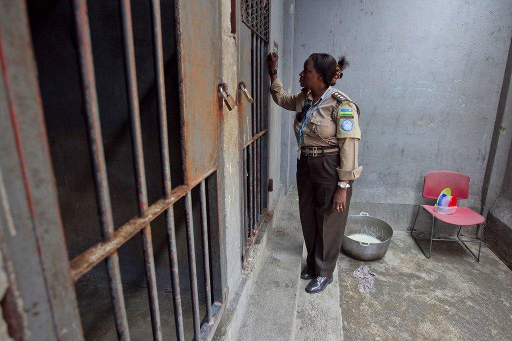 来自卢旺达的一名惩戒干事正在与太子港女子监狱的一名被拘留者进行交谈。