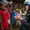 A Chinese police officer deployed to the UN Mission in Liberia (UNMIL), talks to a young girl whilst on patrol (file photo).