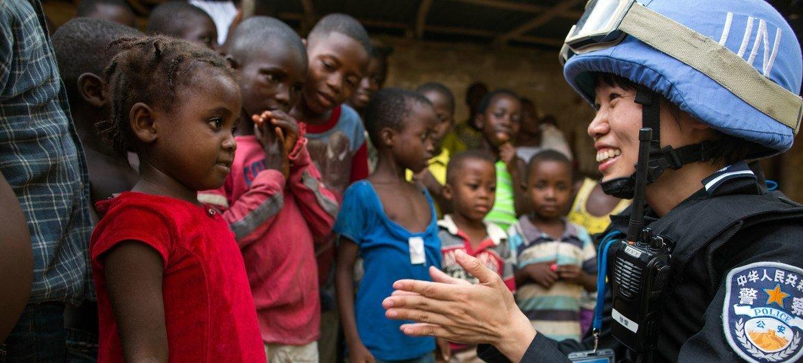 Une officiere de police chinoise déployée au sein de la Mission des Nations unies au Libéria (MINUL), parle à une jeune fille lors d'une patrouille.