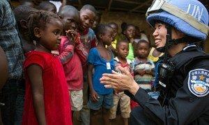 Afisa wa polisi wa Uchina aliyetumwa kwa Misheni ya UN huko Liberia (UNMIL), anaongea na msichana mchanga wakati wa doria.