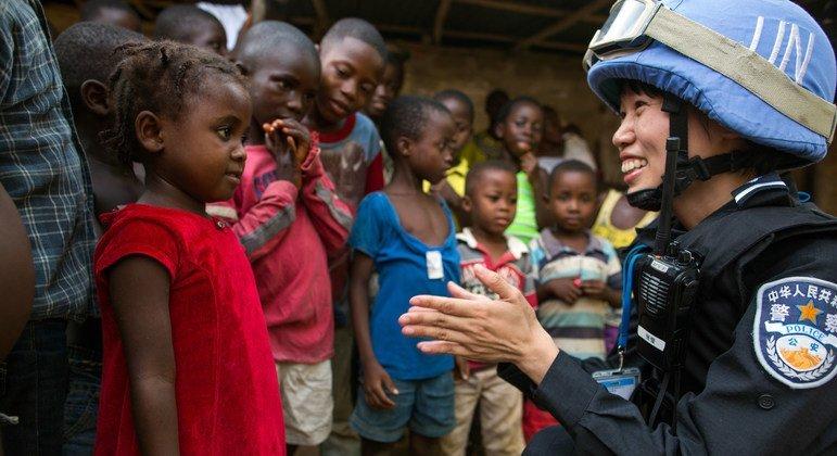Офицер полиции Китая, служащая в составе миротворческого контингента ООН в Либерии, - с местными детьми