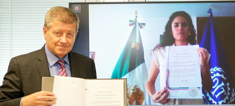 El director general de la OIT y la Secretaria de Trabajo y Seguridad Social de México sostienen el Convenio 189 para proteger a los trabajadores domésticos.