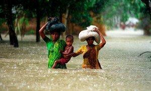 People wade through water during floods in the Kurigram district of Bangladesh.