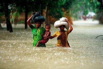 Mujeres vadeando las inundaciones en el distrito de Kurigram en Bangladesh.