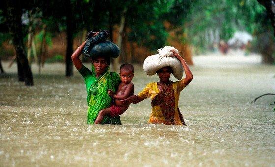 बांग्लादेश के कूरीग्राम ज़िले में आई बाढ़ से होकर गुज़रते हुए कुछ लोग