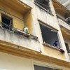 黎巴嫩贝鲁特港发生爆炸,一名年轻人从公寓里向外张望。