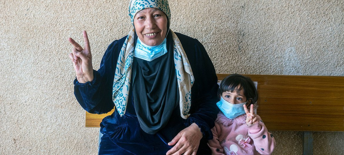 A Syrian refugee gives the 'V for Vaccinated' sign with her granddaughter after receiving her COVID-19 vaccine in Za'atari Refugee Camp.
