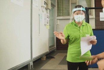 缅甸移民劳工社区卫生志愿者伦伦(左)正在参加防疫工作。