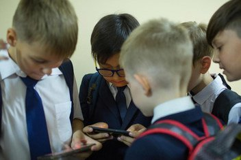 Children playing with their phones, as they wait for class to begin, in Almaty, Kazakhstan (September 2019).