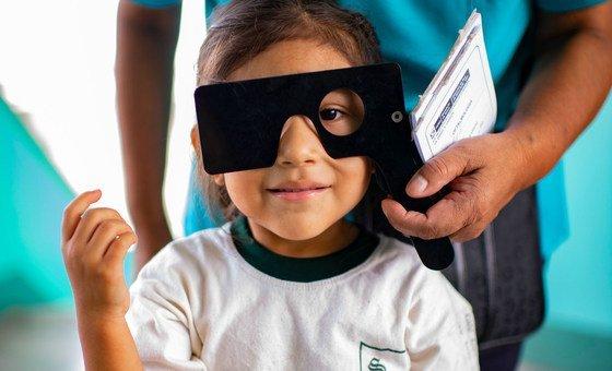 Menina faz exame visual em sua escola em Lima, no Peru