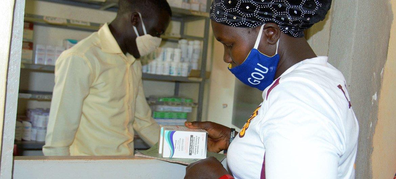 Una mujer que vive con VIH recibe su medicación en un centro de salud de Uganda durante la pandemia de COVID-19.