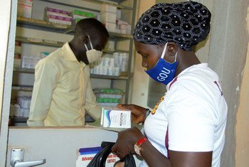 在新冠大流行期间,一名感染艾滋病毒的妇女在乌干达的一个健康中心取药。