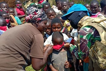 A peacekeeper from MONUSCO's Female Engagement Team distributes face masks at a village in Walungu in the Democratic Republic of the Congo.