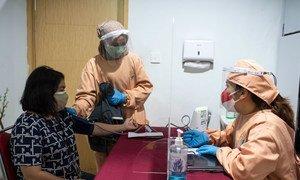 Une femme fait contrôler sa tension artérielle avant de recevoir une injection de rappel contre la Covid-19 en Indonésie.