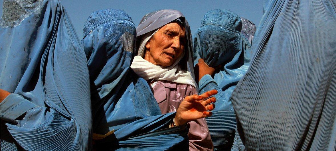 Des femmes afghanes font la queue au point de distribution du Programme alimentaire mondial (PAM) à Herat, en Afghanistan, pour collecter des sacs de pois chiches cassés, de blé et d'huile de cuisson distribués par le PAM.