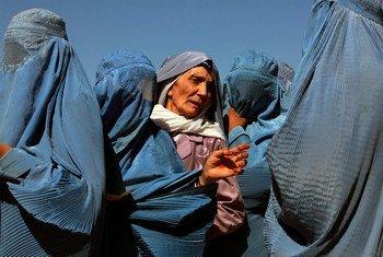 امرأة أفغانية تقف في طابور لتلقي مساعدات من برنامج الأغذية العالمي. في حيرات تقف النساء لجمع أكياس الحمص والقمح وزيت الطبخ التي يوزعها برنامج الأغذية العالمي