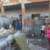 In Binnish in the Syrian Arab Republic, internally displaced people from Idlib live in a destroyed school while a tanker provides them with water that children transport with small containers.