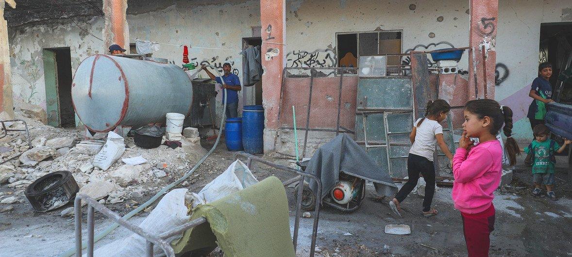 في بننيش في الجمهورية العربية السورية، يعيش النازحون داخلياً من إدلب في مدرسة مدمرة بينما تزودهم ناقلة بالمياه ومن ثم ينقلها الأطفال بحاويات صغيرة.