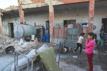 在叙利亚的宾尼什,来自伊德利卜的国内流离失所者住在一所被摧毁的学校中,儿童需要用容器运送饮用水来维持生存。