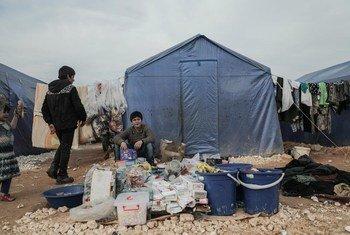 冲突导致近百万叙利亚西北部居民流离失所。照片中一个年轻的男孩在伊德利卜北部村庄的营地帐篷前等待购买东西的人。