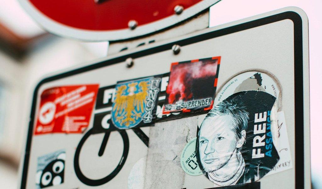 Un autocollant avec le visage de Julian Assange collé sur un panneau urbain