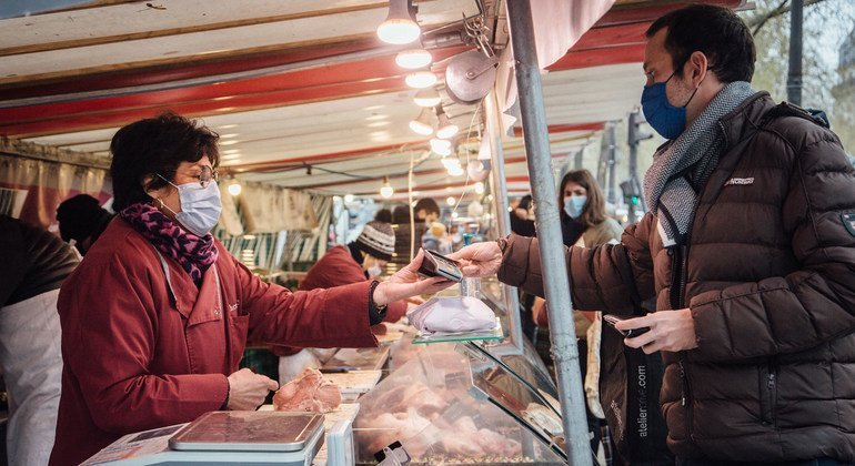 Personas con mascarillas contra el COVID-19 en un mercado de París, Francia.