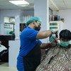 पाकिस्तान के कराची शहर में एक नाई मास्क पहनकर ग्राहक के बाल काट रहा है.