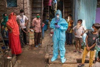 Un coordonnateur chargé de la sensibilisation à la Covid-19 à Mumbai, en Inde, conseille une communauté sur les précautions à prendre.