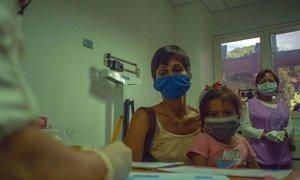 أم تجلب ابنتها الصغيرة إلى موعد مع الطبيب في أحد المراكز الصحية في فنزويلا.
