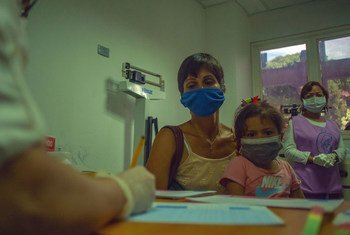 A mother brings her young girl to a medical appointment at a health centre in Caracas, Venezuela.