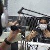 Crianças em Espanha fazendo programa de rádio que serve uma comunidade de Sevilha