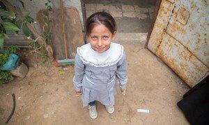 一个女孩站在加沙可汗尤尼斯巴勒斯坦难民营的家门前。