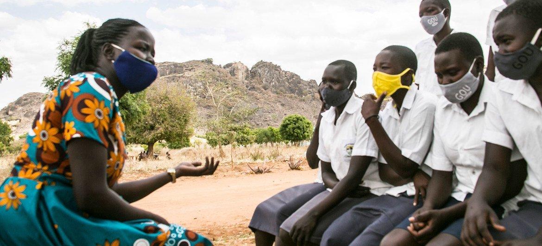 Estudiantes en Uganda hablan sobre la violencia contra las mujers con una maestra.