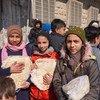 أطفال يتلقون الخبز من مخبز في حلب، سوريا، حيث يساعد برنامج الأغذية العالمي في توزيع المواد الغذائية.
