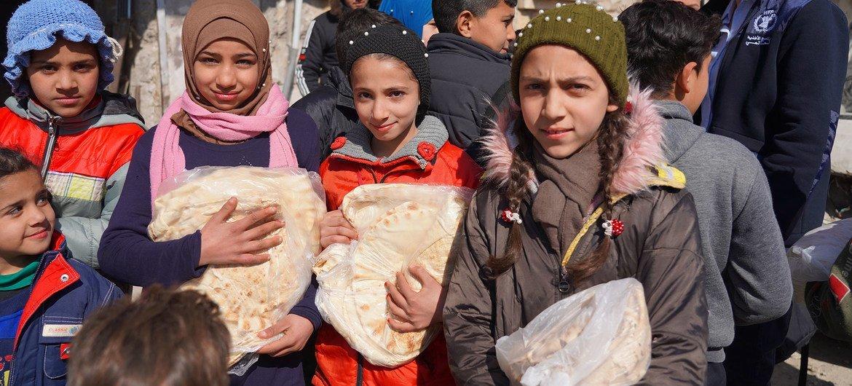 Niños reciben pan en Alepo, Siria, donde el PMA ayuda en la distribución de comida.