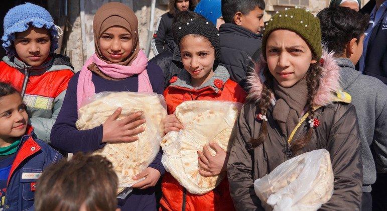 أطفال يحصلون على أرغفة الخبز من أحد المخابز في حلب، حيث يساعد برنامج الأغذية العالمي في توزيع الطعام.