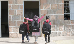 أطفال صغار يسيرون في تعز المتضررة بسبب الصراع في اليمن وقد حصلوا على حقائب مدرسية جديدة في كانون الثاني-يناير 2020