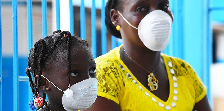 किसी अफ्रीकी देश में एक महिला अपनी बेटी के साथ एक स्वास्थ्य केंद्र पर कोविड-19 से बचाव के लिए एहतियाती उपाय करती हुई.