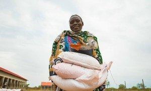 Mujer cargando costales de semillas distribuidos a las familias en Sudán del Sur durante la pandemia de COVID-19