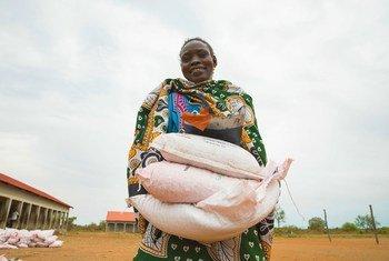 Mwanamke akibeba magunia ya mbegu zilizosambazwa kwa familia huko Sudani Kusini wakati wa janga la COVID-19.
