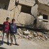 طفلان يقفان أمام مبنى مدمر في بنغازي (من الأرشيف)